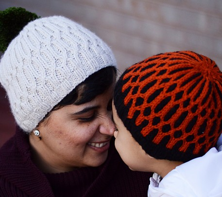 Free knitting patterns for Uljhan Hats - This fun beanie features a play on a 2x2 rib, using two colors of yarn. It also uses a 1x1 cable at specified intervals, to form a pretty pattern over the body of the beanie.